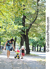 children and mom have fun at park while learning to ride...