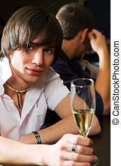 Young man relaxing in a bar - Young man drinking champagne...