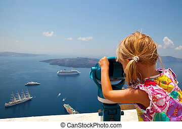 Girl looking with binoculars in Thira, Santorini, Greece -...