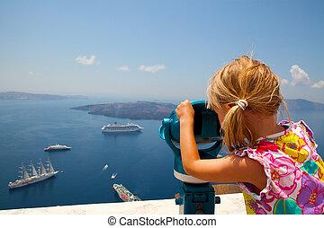 Girl looking with binoculars in Thira, Santorini, Greece -...