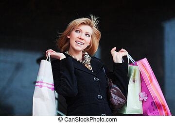 Young woman with shopping bags against of store window