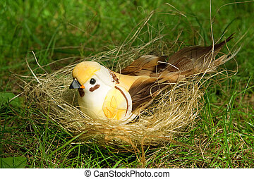 Toy bird in the nest, on the green grass, close-up
