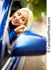 Make up on the move - Photo of happy woman looking into car...