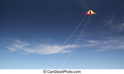 Kite soaring 1 - Motley kite flying in blue sky. Near white...