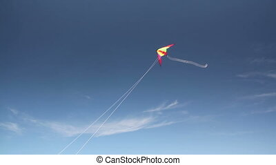 Kite soaring 3 - Motley kite flying in blue sky