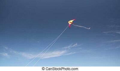 Kite soaring 3 - Motley kite flying in blue sky