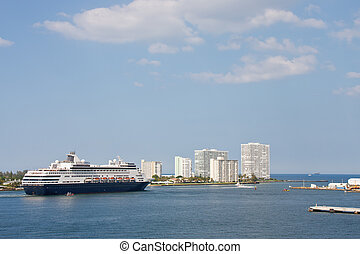 A huge luxury cruise ship cruising through channel past white condos