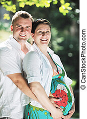 Happy pregnant couple at beautiful sunny day in park - Happy...