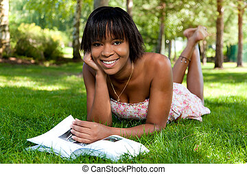 Outdoor portrait of young black woman reading a book -...