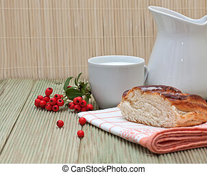 pitcher of milk and a piece of cake on a wooden table