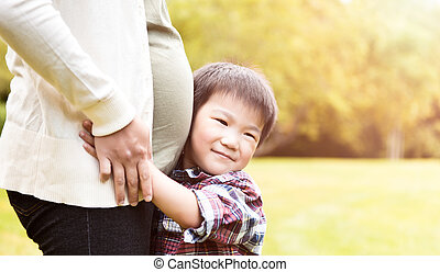 Pregnant Asian mother and her son - A shot of an Asian boy...