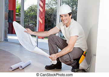 Smiling man with blueprint