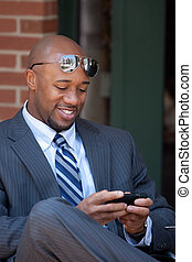 Modern Business Man Texting - A good looking African...