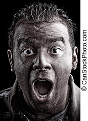 Scared Man Screaming - A frightened man with dark skin has a...