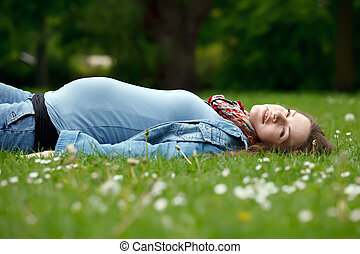 Pregnant woman relaxing in the park