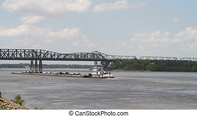 Mississippi River Industry - Tugboat pushes a barge on the...