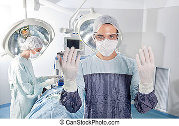 Male surgeon asking for gloves