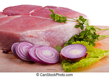 Piece of crude meat with onion on chopping board
