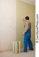 worker in blue overalls glues wallp - worker is standing on...