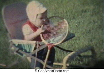 Baby Boy Chews On Badminton Racket - A cute baby boy plays...
