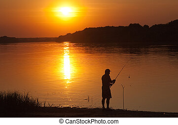 The man fishes on decline of day on river bank