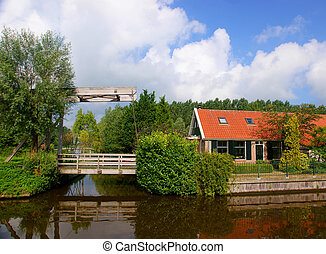Dutch house with bridge - Dutch house near the river, with a...