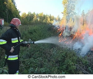 Uniformed firefighter with the hose in the hands fighting...