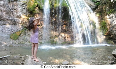 outstretched arms by the waterfall - Woman with outstretched...
