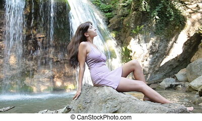 young woman by the waterfall