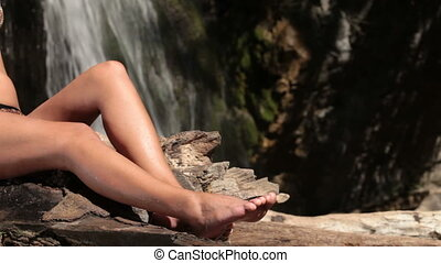 female feet by the waterfall
