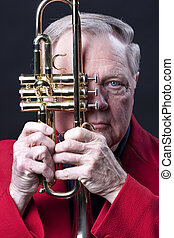 A gold colored brass trumpet being held close to face  by a senior man trumpet player in the vertical format with a black background.