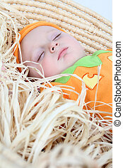 Pumpkin baby - Baby dressed in a pumpkin costume sleeping in...