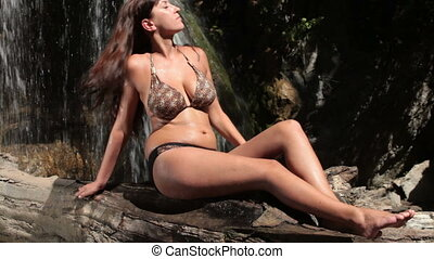 hot summer day by waterfall - tanned young woman in a bikini...
