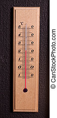 Old thermometer measuring in celsius. On the black wall.