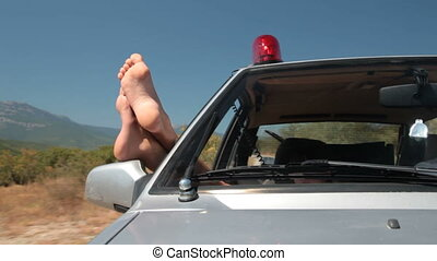 police car in the summertime - female feet stick out from...