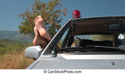 Summer police patrol - Woman hanging out legs from window...