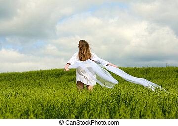 Young woman in a field - Happy young woman walking in an...