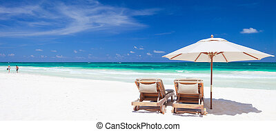 Caribbean coast - Two chairs and umbrella on stunning...