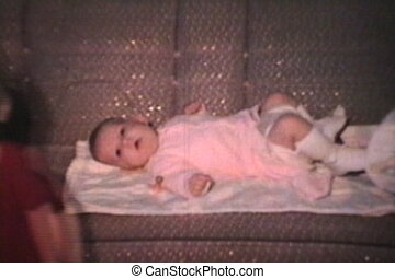 Baby Laying On Sofa 1968 Vintage - A cute baby girl lays on...