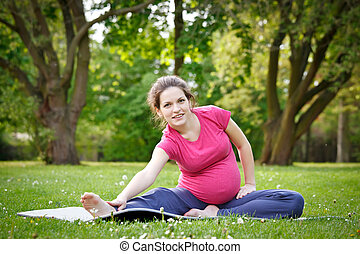 Pregnant woman exercising in the park