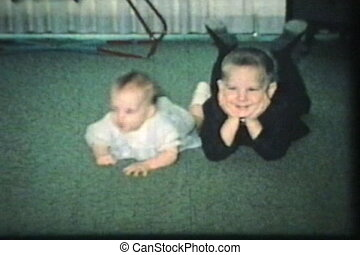 Brother And Sister Laying On Carpet - A little boy and his...