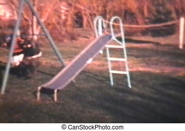 Children Playing On Swings (1969) - Three young kids play on...