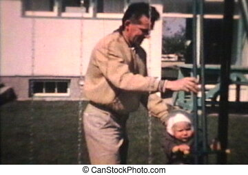 Dad Pushes Little Boy On Swing 1963 - A proud dad pushes his...