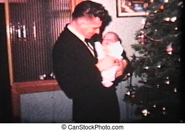 Dad With Baby By Christmas Tree - A proud dad holds his baby...