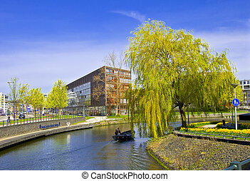 Amsterdam. Modern residential areas. Green Tree at the edge of the quay on the canal.