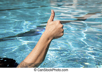 thumb up in the swimming pool