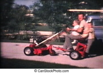 Kids On Riding Lawn Mower 1967 - A loving dad takes his two...