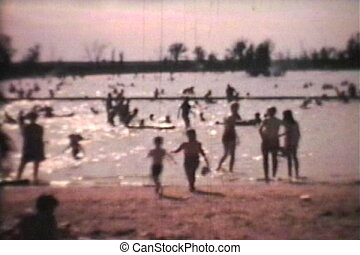 Kids Playing At The Beach 1966 - A shot of a crowded beach...