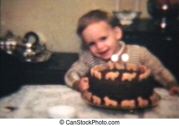 Boy Blows Out Candles On Cake - A cute little boy blows out...