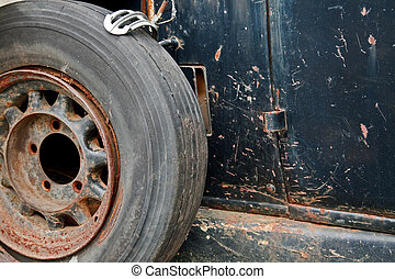 rusty wheel on the side of an old car